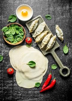 Zubereitung roher gedza-knödel mit spinat und chili
