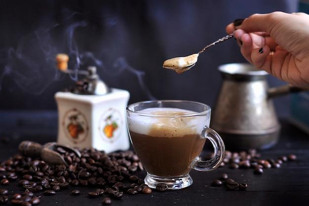 Zubereitung von aromatischem kaffee mit schaum und milch. dunkles foto. türkischer kaffee. kopieren sie spce