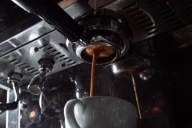 Zubereitung von espresso. kaffee fließt aus der kaffeemaschine in die weiße tasse. professionelle kaffeezubereitung.