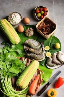 Zubereitung von flatlay cooking zutaten, herstellung von spinatsuppe (sayur bayam) und shrimp tempura. zusammensetzung rohe frische zutaten mit kopienraum für text/werbung