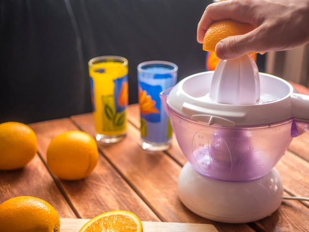 Zubereitung von frischem orangensaft smoothie mit saftpresse auf einer holzoberfläche