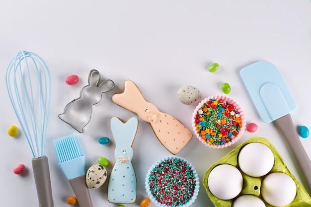 Zubereitung von lebkuchen. osterplätzchen in form eines lustigen kaninchens, werkzeuge zur herstellung von lebkuchengebäck, farbige streusel. osterkonzept.
