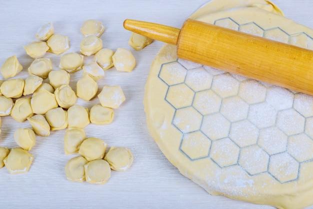 Zubereitung von pelmeni zu hause in der küche zubereiten, kochen, hausgemachte ravioli, pelmeni oder knödel mit fleisch zubereiten