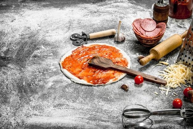 Zubereitung von pizza. auf einem rustikalen hintergrund.