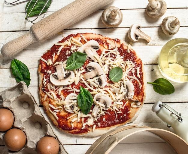Zubereitung von pizza mit verschiedenen zutaten. auf einem weißen holztisch.