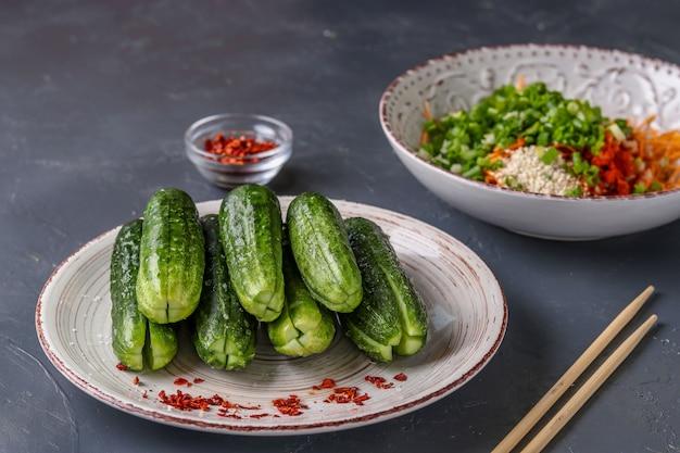 Zubereitung von produkten für das kochen des traditionellen koreanischen gurkenkimchisnacks: gurken im querschnitt im vordergrund