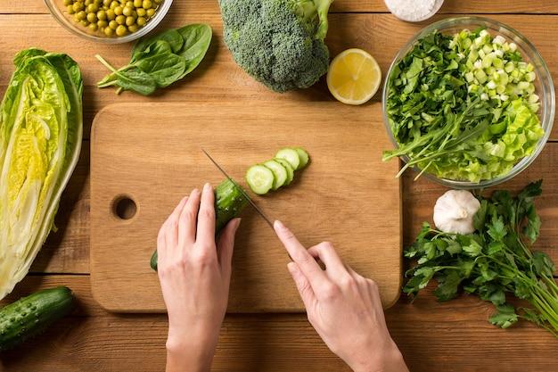 Zubereitung von salat aus frischem gemüse. weibliche hände schneiden die gurke mit einem messer auf einem schneidebrett.
