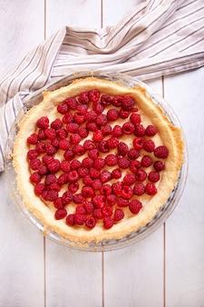 Zubereitung von shortbread pie mit himbeeren auf einem weißen holztisch
