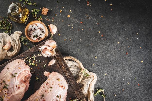 Zubereitung von speisen, mittagessen. fleisch. hähnchenfilet mit haut, roh. auf einem schneidebrett mit gewürzen, thymian, knoblauch, olivenöl, salz, pfeffer. holzbrett, schwarzer steinhintergrund. copyspace draufsicht