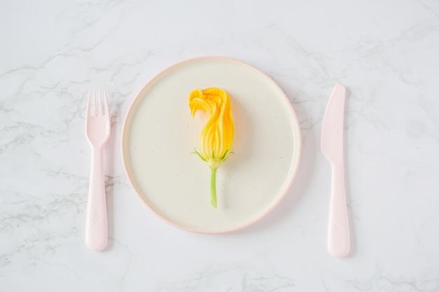 Zucchini blüht in einer platte auf einem hellen hintergrund
