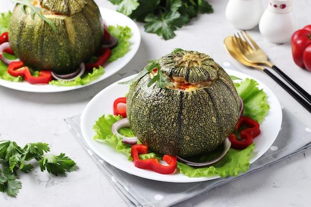 Zucchini gefüllt mit reis und gemüse auf hellgrauem hintergrund. vegetarisches essen. nahaufnahme.