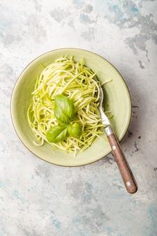 Zucchini-gemüsenudeln - grüne zoodles oder zucchinispaghetti auf teller über grauem hintergrund.