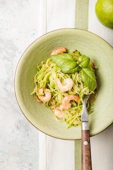 Zucchini-gemüsenudeln - grüne zoodles oder zucchinispaghetti mit garnelen auf teller über grauem hintergrund.