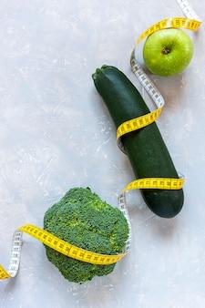 Zucchini, grüner apfel und brokkoli und zentimeter. frisches obst und gemüse
