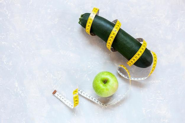 Zucchini, grüner apfel und zentimeter. frisches obst und gemüse