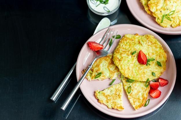 Zucchini-krapfen, vegetarische zucchini-krapfen, serviert mit frischen kräutern und saurer sahne. mit erdbeeren und frühlingszwiebeln garniert. auf einem dunklen tisch.