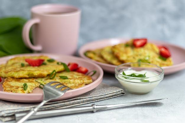 Zucchini-krapfen, vegetarische zucchini-krapfen, serviert mit frischen kräutern und saurer sahne. mit erdbeeren und frühlingszwiebeln garniert. auf einem hellgrauen tisch.