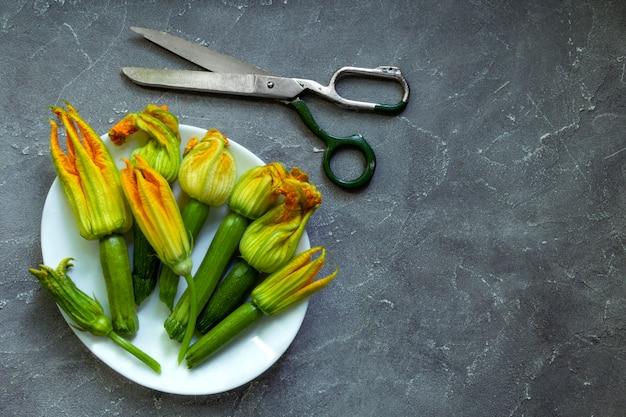 Zucchini mit blumen im weißen teller und in der schere auf dem alten grauen hintergrund. flache lage, draufsicht. speicherplatz kopieren