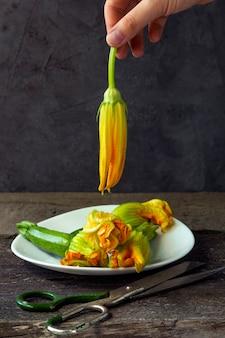Zucchini mit blumen in weißem teller und schere auf dem alten holztisch. weibliche hand, die eine blüte hält