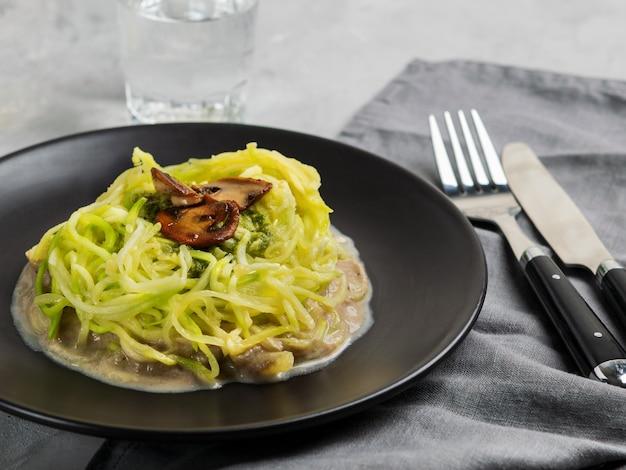 Zucchini-nudeln oder zoodles mit sahniger pilz-pesto-sauce.