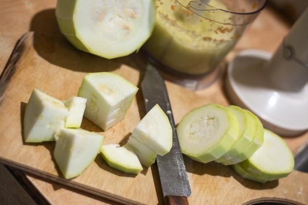 Zucchini schneiden für smoothies. vorbereitungen für den winter eine mischung aus gemüse.