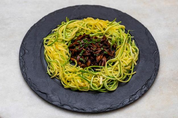 Zucchini-spaghetti mit shimeji auf schwarzer steinplatte.
