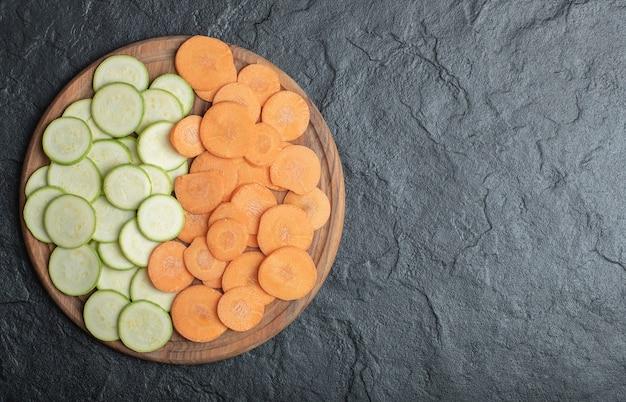 Zucchini und karottenscheiben auf schwarzem hintergrund. hochwertiges foto