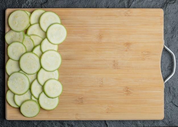Zucchini und scheiben im holzbrett auf schwarzem hintergrund. hochwertiges foto