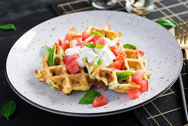 Zucchini-waffel, zucchini-krapfen, die auf einem waffeleisen kochen, vegetarische zucchini-waffeln mit tomaten, sauerrahm und basilikum in einem weißen teller.
