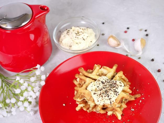 Zucchini-waffeln auf rotem teller mit sauce und gewürzen,