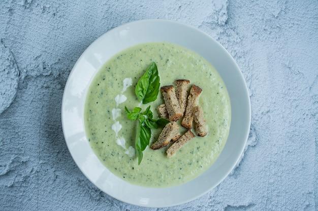Zucchinicremesuppe gedient in einer weißen platte.