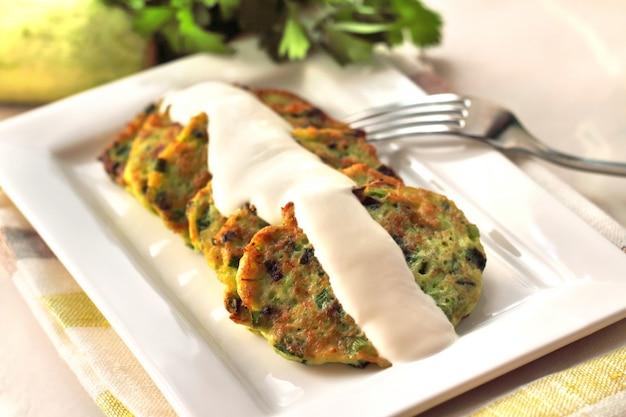 Zucchinipfannkuchen mit frühlingszwiebeln und sauerrahm