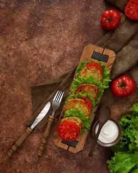 Zucchinipfannkuchen mit grünem salat, frischen tomaten und sauerrahm