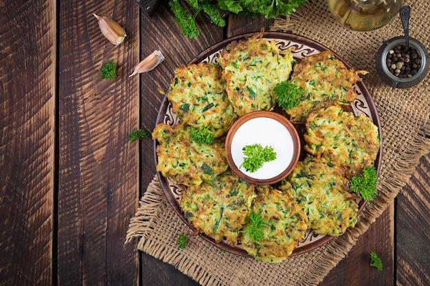 Zucchinipuffer. vegetarische zucchini-pfannkuchen mit soße auf holzhintergrund. gesundes essen. ansicht von oben, flach