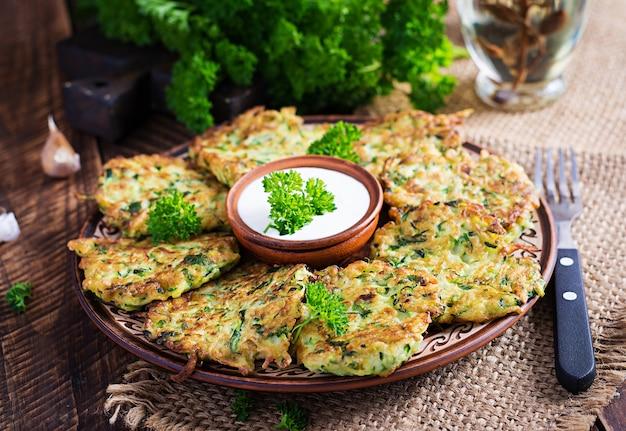 Zucchinipuffer. vegetarische zucchini-pfannkuchen mit soße auf holzhintergrund. gesundes essen.