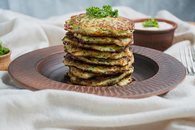 Zucchinistückchen gedient mit frischen kräutern und sauerrahm, draufsicht.