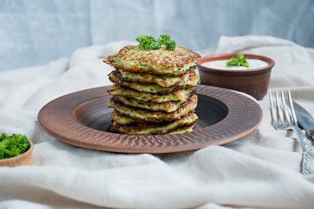 Zucchinistückchen, vegetarische zucchinipfannkuchen, serviert mit frischen kräutern und saurer sahne.