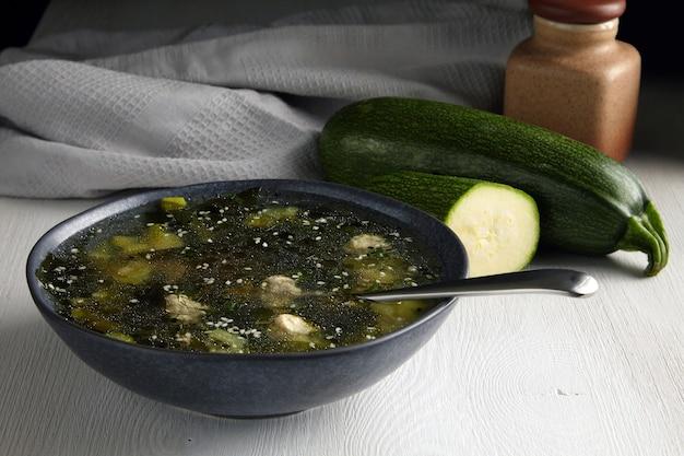 Zucchinisuppe mit fleischbällchen auf einem weißen tisch