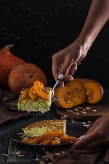 Zucchinitorte mit gebackenem kürbis auf einer spachtel in den händen der frauen in der küche, auf einer dunklen hölzernen copyspace nahaufnahme mit copyspace.