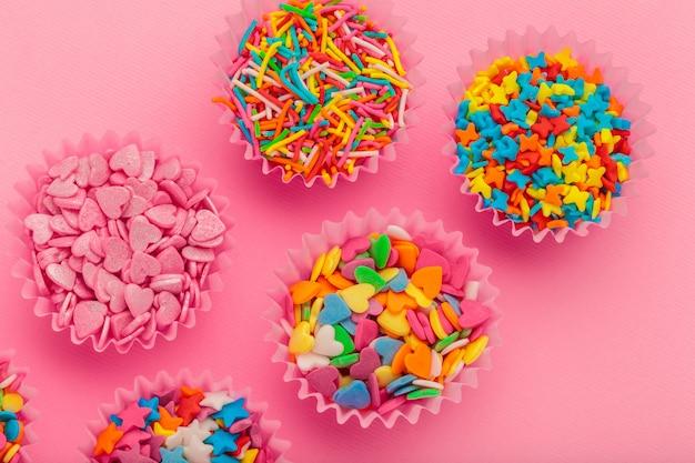 Zucker besprüht lebensmittel auf rosa pappe