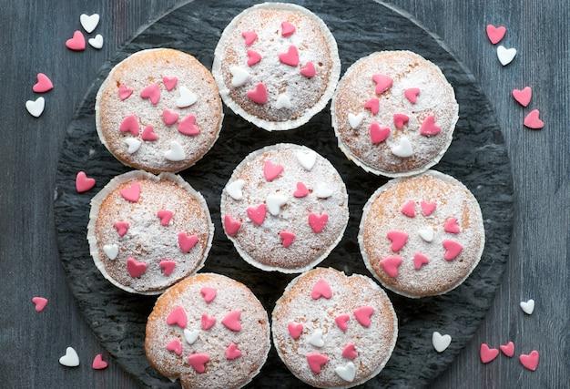 Zucker besprühte muffins mit rosa und weißen fondantzuckerglasurherzen