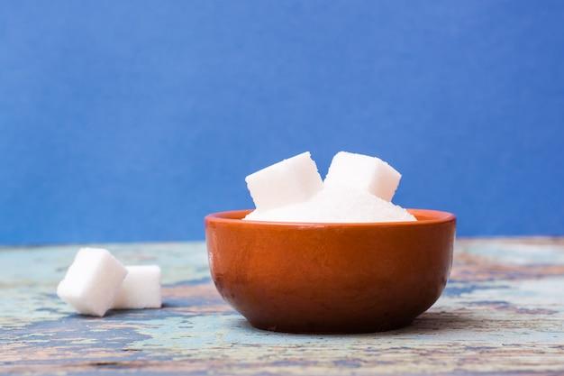 Zucker granuliert und raffinierter zucker in einer schüssel auf einem holztisch auf einem blauen hintergrund