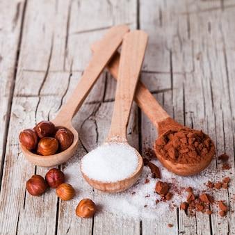 Zucker, haselnüsse und kakaopulver in löffeln