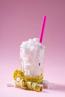 Zucker im glas mit maßband auf auf rosa hintergrund