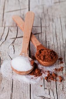 Zucker und kakaopulver in löffeln