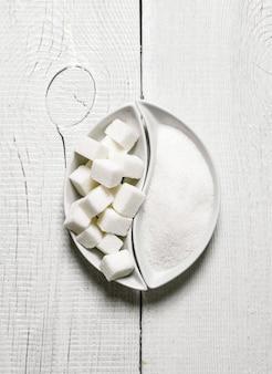 Zucker und raffinierter zucker. auf einem weißen holztisch.