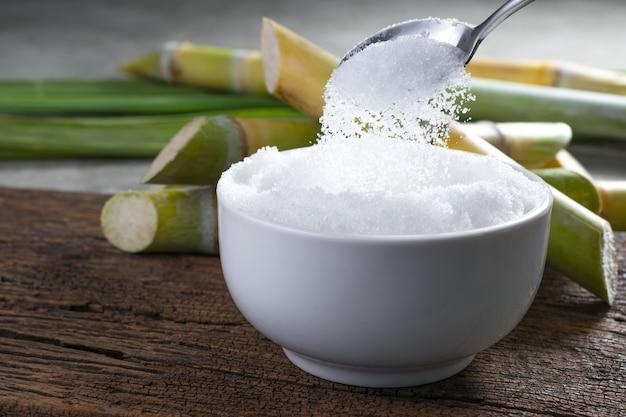 Zucker wird aus dem löffel in eine schüssel gegossen leere bereit für ihre produkt-display oder montage.