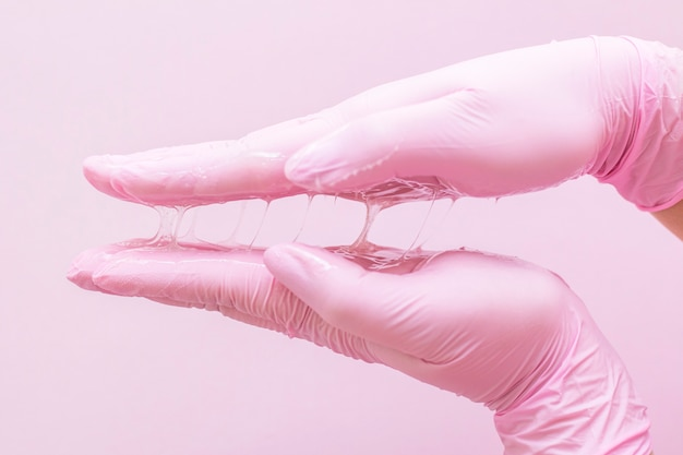 Zucker zur enthaarung in händen in rosa handschuhen auf rosa
