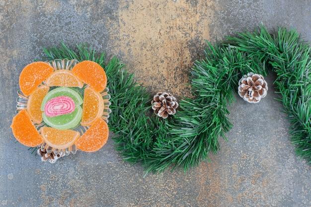 Zuckerhaltige fruchtgelee-bonbons mit tannenzapfen und bündel weihnachtsbaum. hochwertiges foto