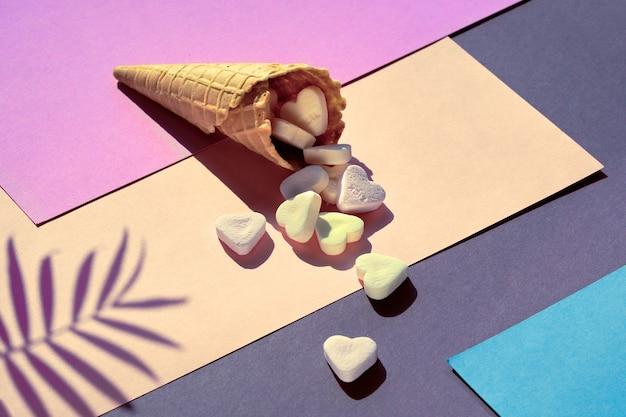 Zuckerherzen in der eiswaffeltüte auf lila